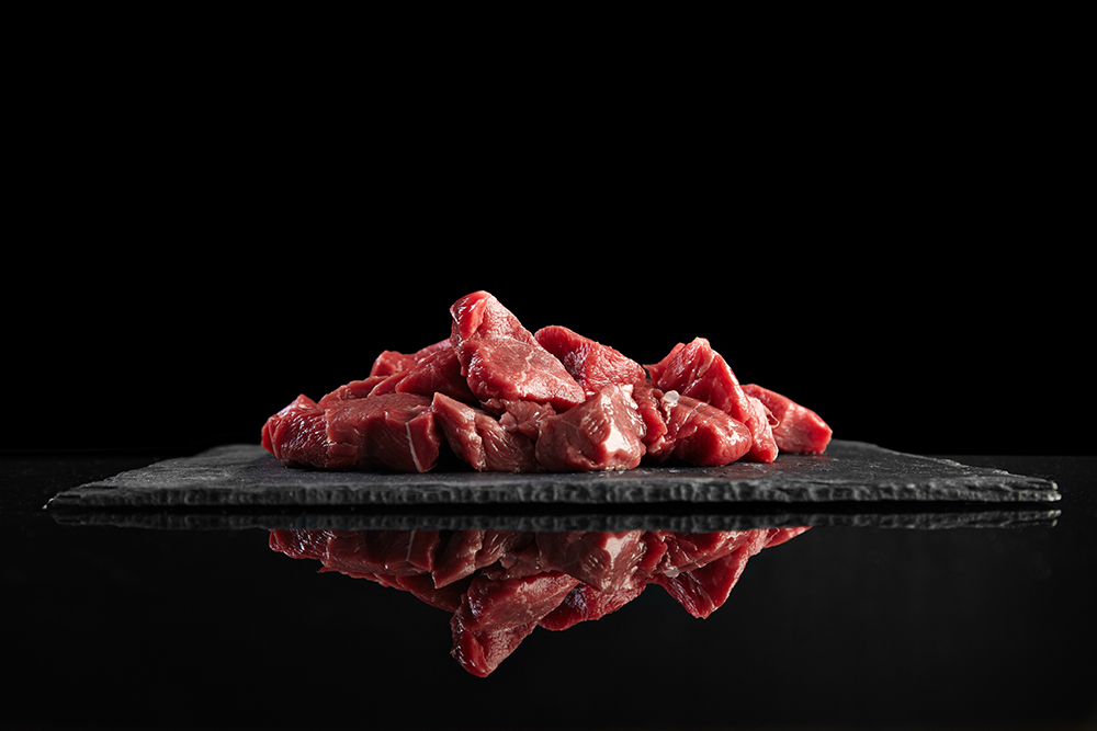pieces raw fresh meat isolated black stone board mirrored side view